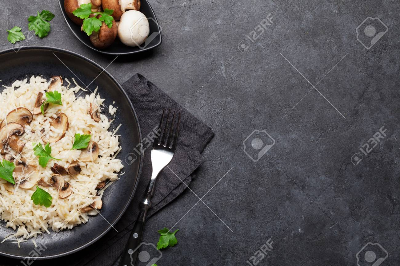 Delicious mushrooms risotto dressed with parmesan cheese and parsley. Top view with copy space - 120470499