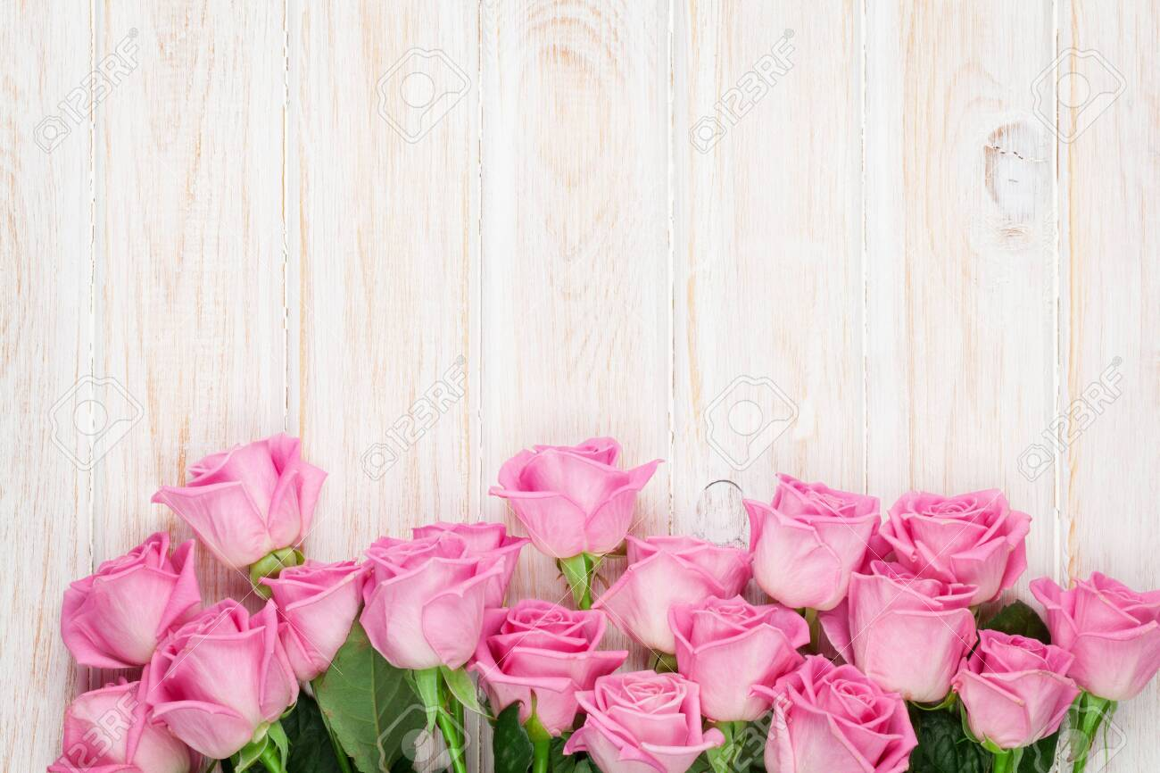 Pink roses over wooden table. Top view with copy space for your text - 120720100