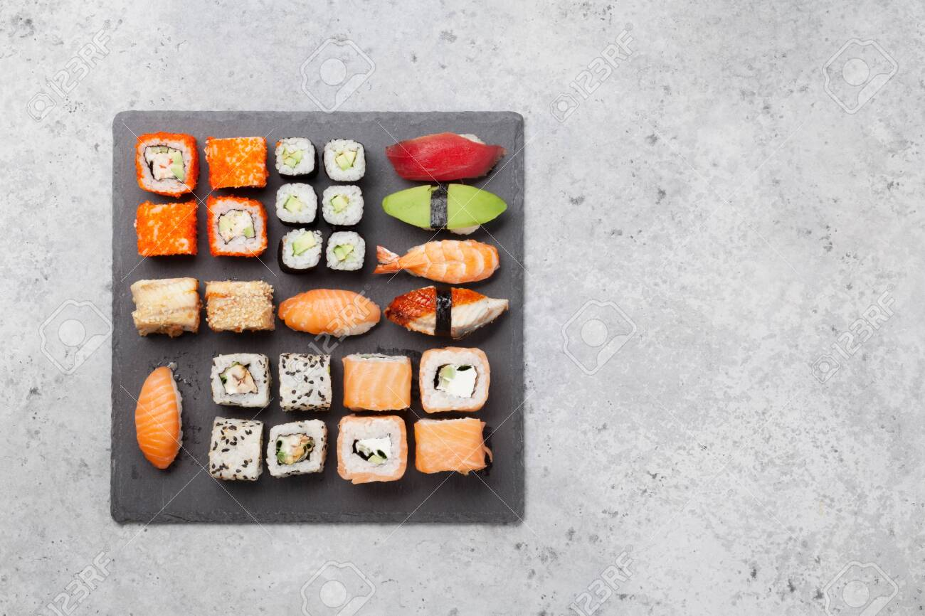 Japanese sushi set. Sashimi, maki rolls. On plate over stone background. Top view flat lay with copy space for your text - 125883347