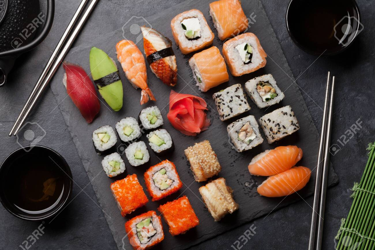 Japanese sushi set. Sashimi, maki rolls and green tea. On slate board over dark stone background - 125957770