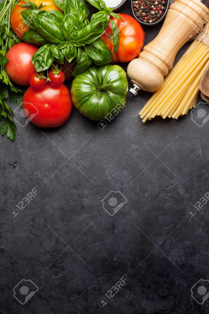 Pasta, tomatoes and herbs. Cooking ingredients on stone table. Top view with copy space. Flat lay - 128759142