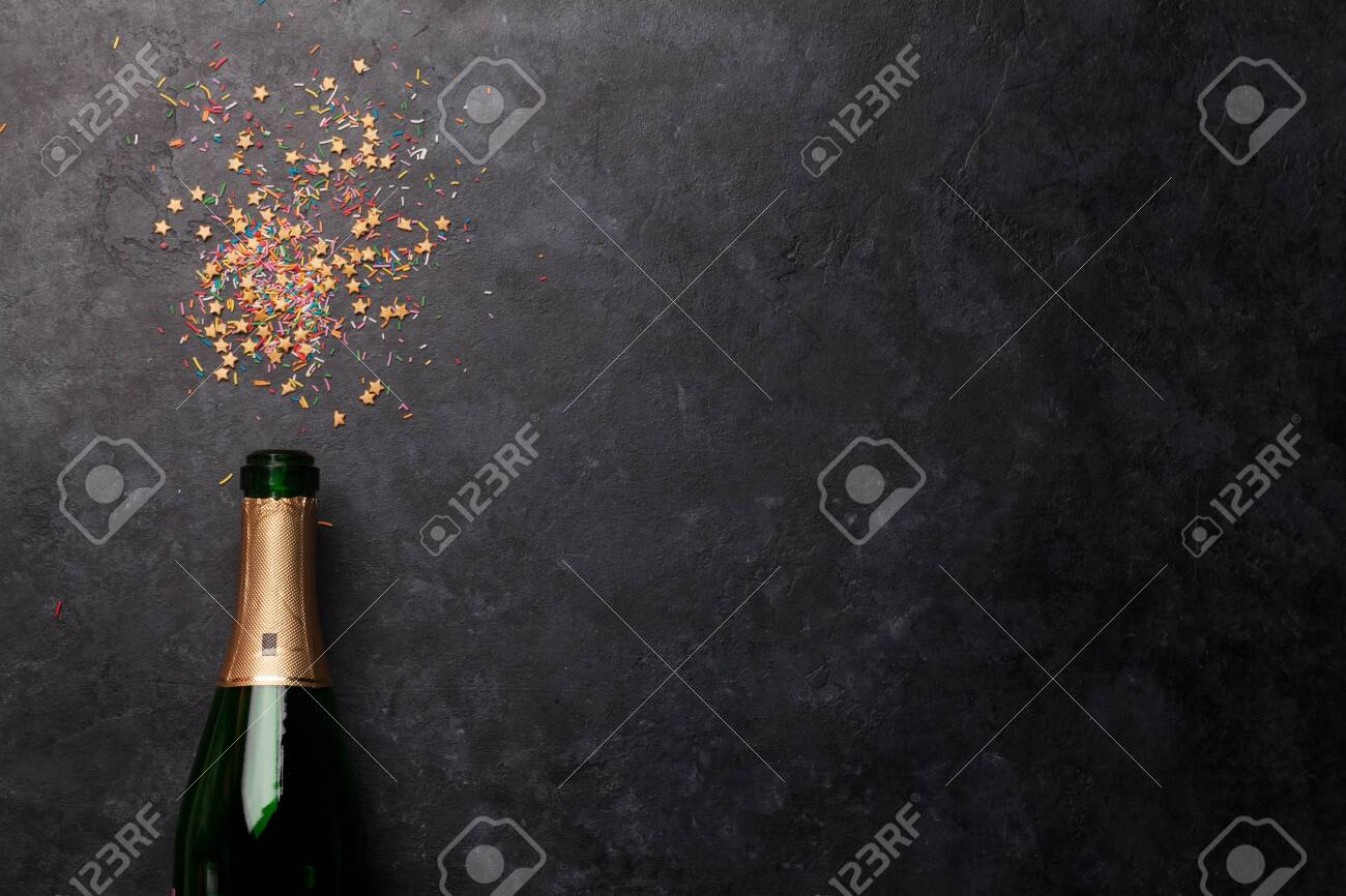 Champagne bottle and sweets holiday template. Christmas, Birthday or Valentines'day backdrop. Top view with space for your greetings - 132779158