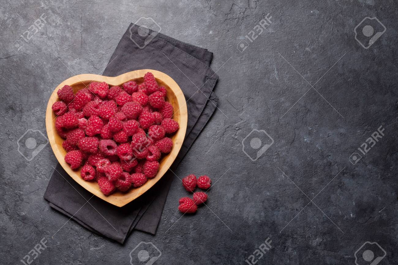 Fresh ripe garden raspberry in heart shaped bowl on stone table. Top view with copy space - 133190875