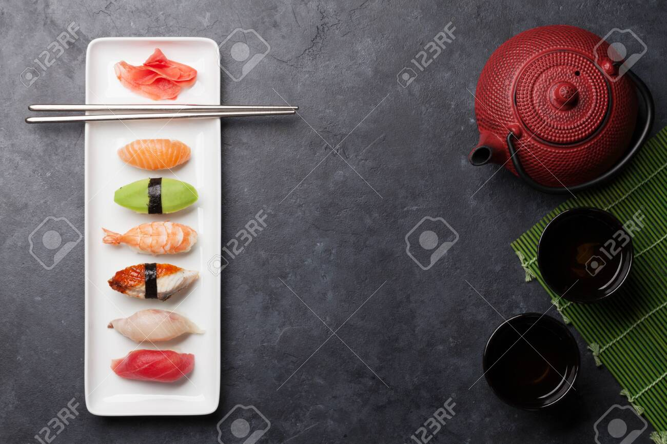 Japanese sushi set. Sashimi, maki rolls and green tea. On plate over stone background with space for your text. Top view flat lay - 134983603