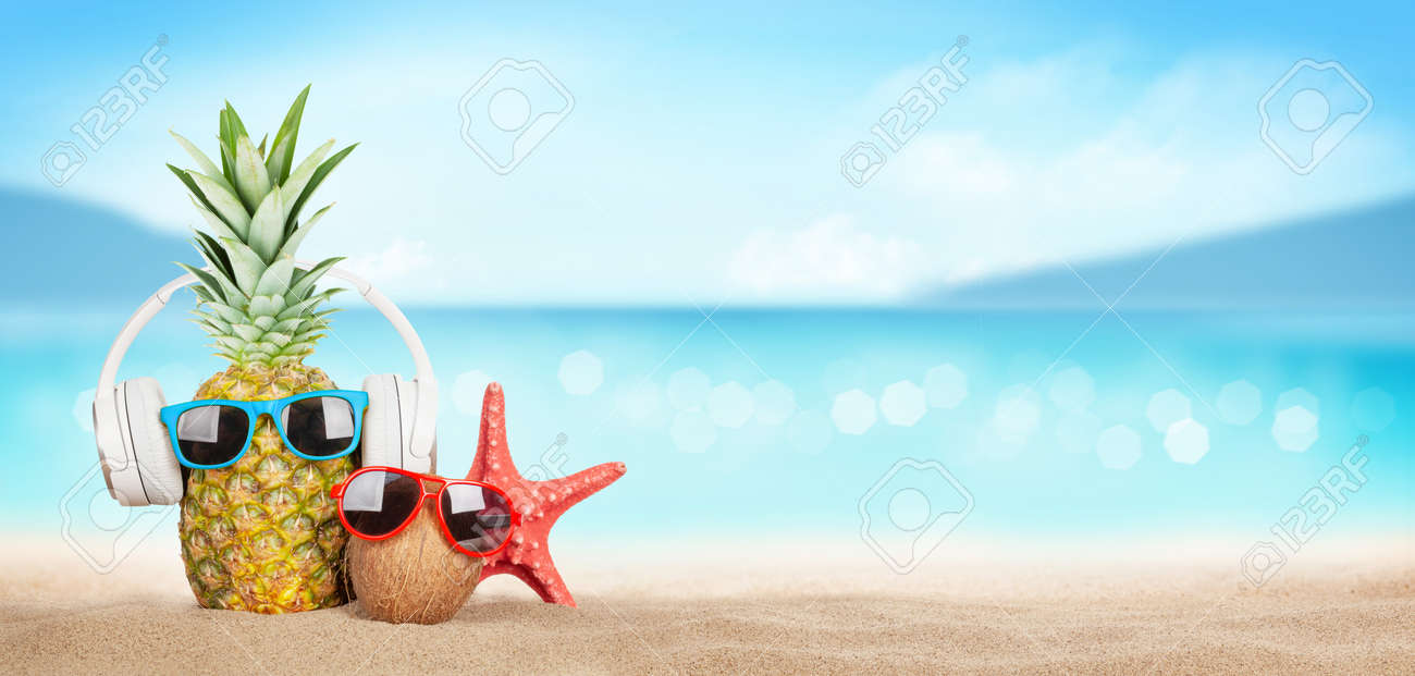 Summer tropical sea with sparkling waves, pineapple and coconut with sunglasses and headphones on hot sand beach. Travel and vacation concept with copy space - 148380272