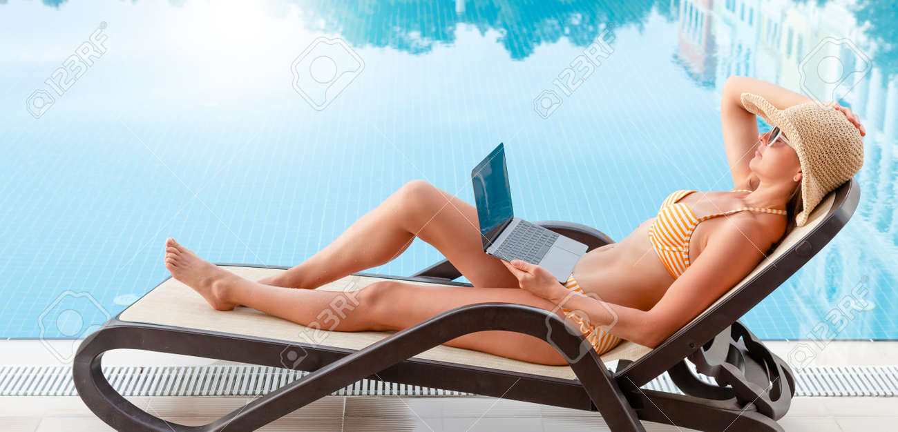 Young woman using laptop for remote work or education near a swimming pool. With copy space for your text or app - 169317590