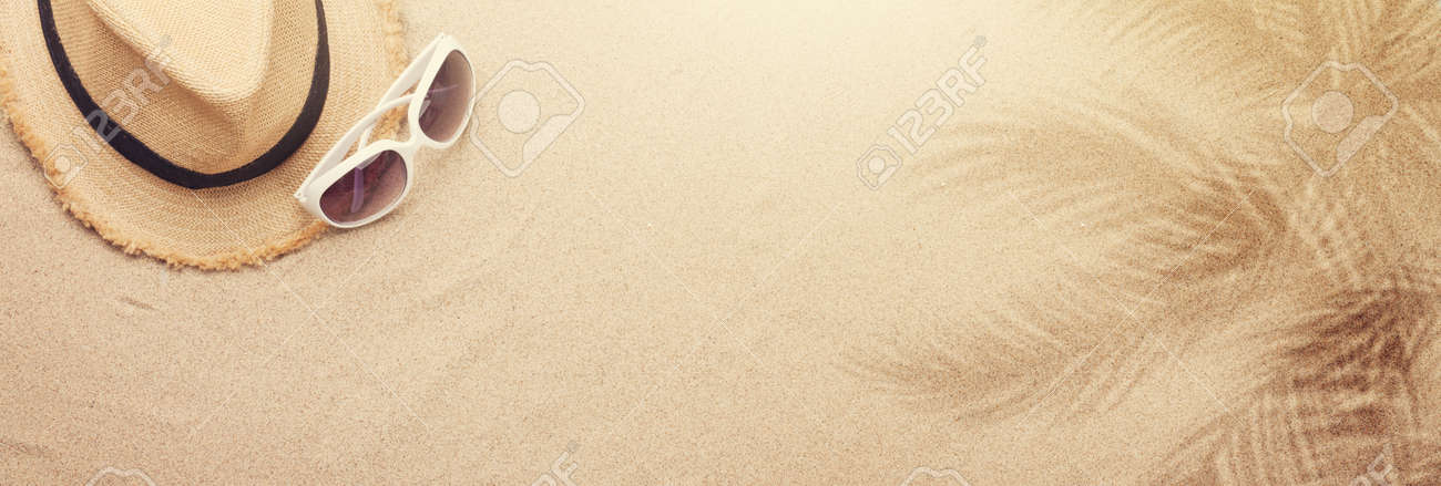 Travel vacation background concept with sunglasses and beach hat on sand backdrop. Top view with copy space. Flat lay - 169317596