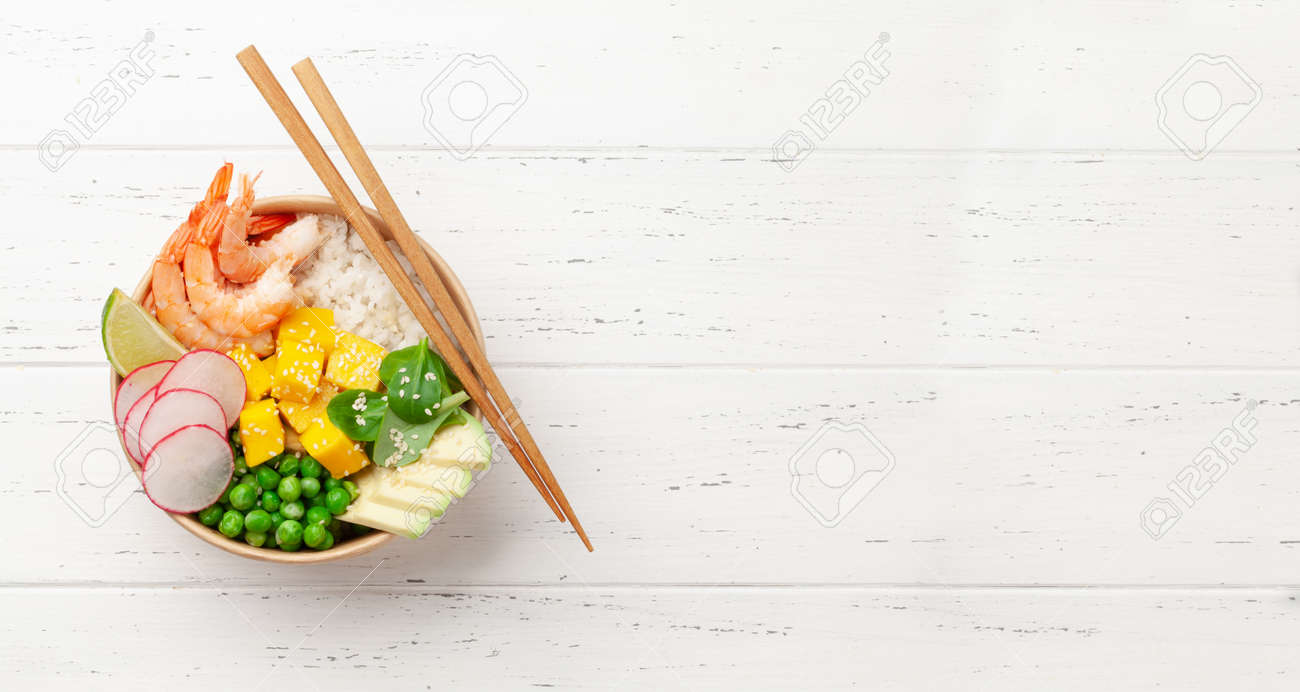 Poke bowl with shrimps, avocado and mango. Traditional hawaiian meal. Top view flat lay with copy space - 169549609