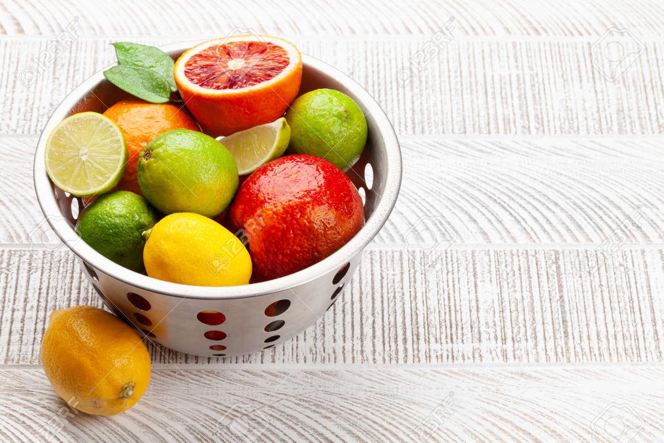 Various fresh citrus fruits in colander. Bood orange, lime, lemon. With copy space - 169549618
