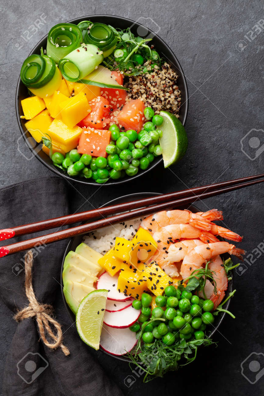 Poke bowls with shrimps, salmon, avocado and mango. Traditional hawaiian meal. Top view flat lay - 169549652