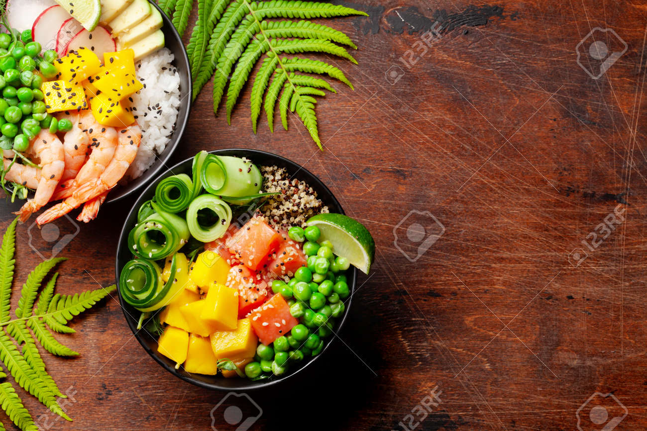 Poke bowls with shrimps, salmon, avocado and mango. Traditional hawaiian meal. Top view flat lay with copy space - 169549730