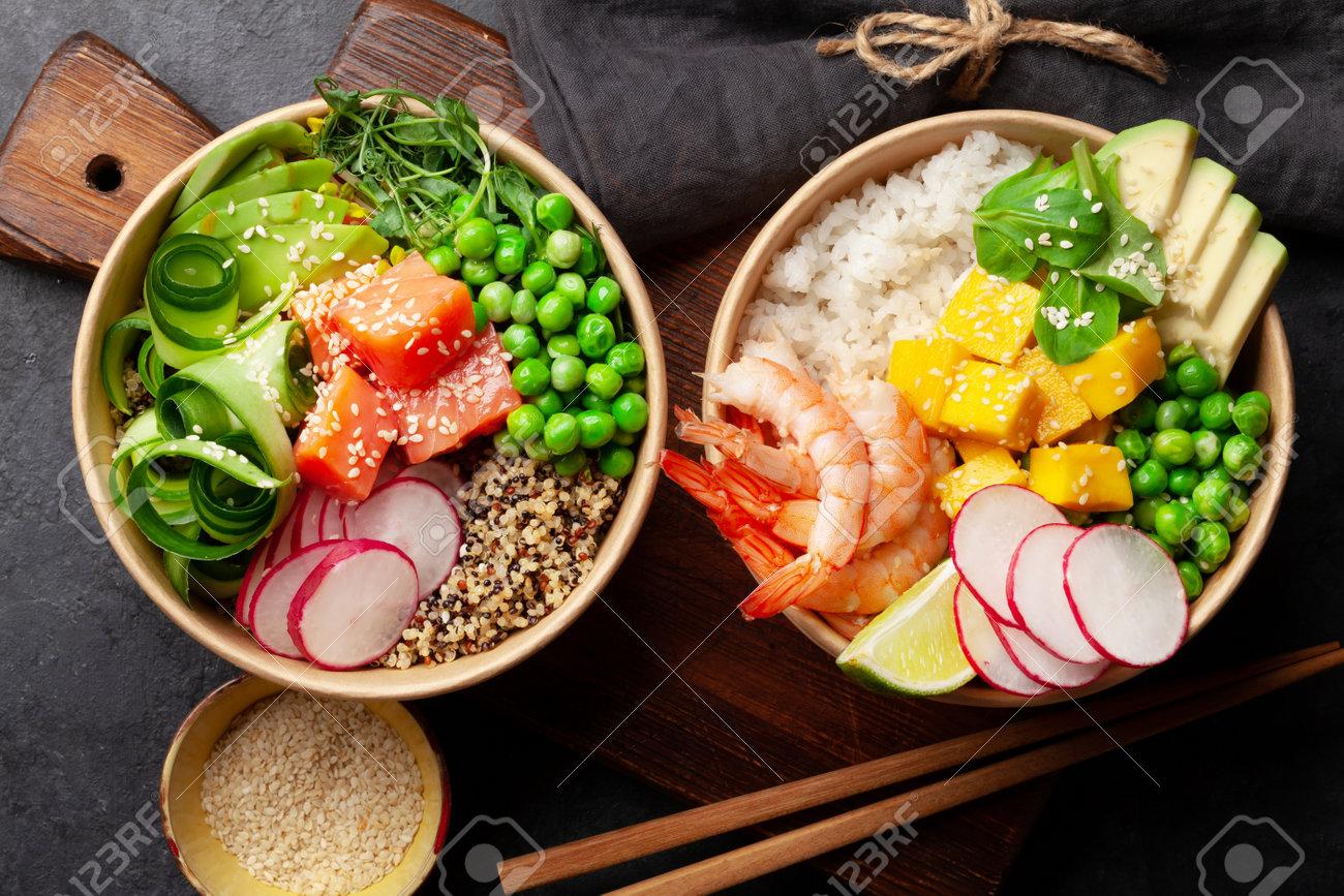 Poke bowls with shrimps, salmon, avocado and mango. Traditional hawaiian meal. Top view flat lay - 169549784