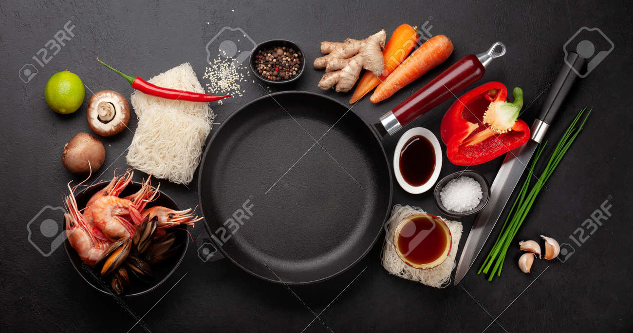 Ingredients for wok cooking with stir fried noodles, shrimps and vegetables on stone background. Top view flat lay with copy space - 169549804