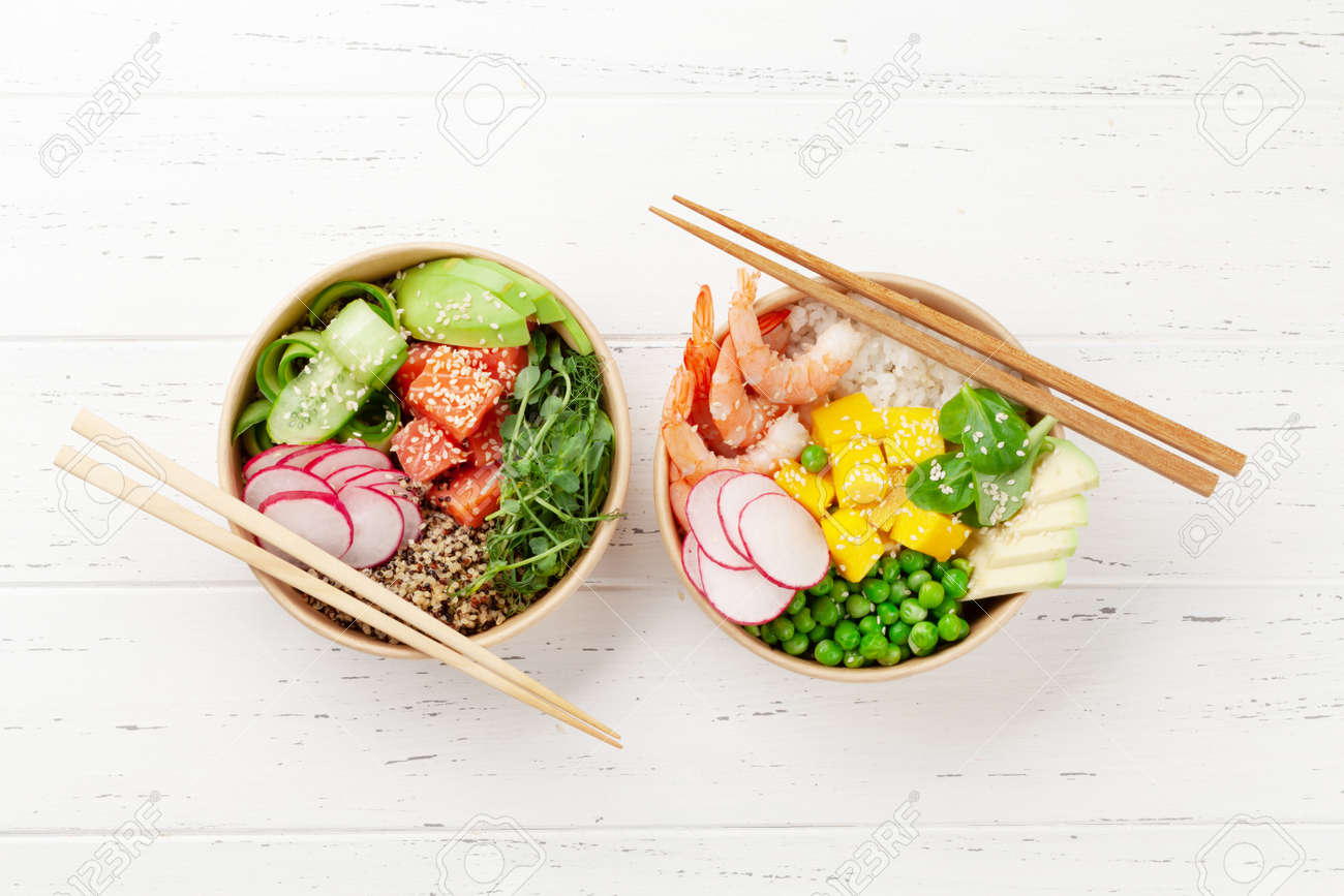 Poke bowls with shrimps, salmon, avocado and mango. Traditional hawaiian meal. Top view flat lay - 169549819