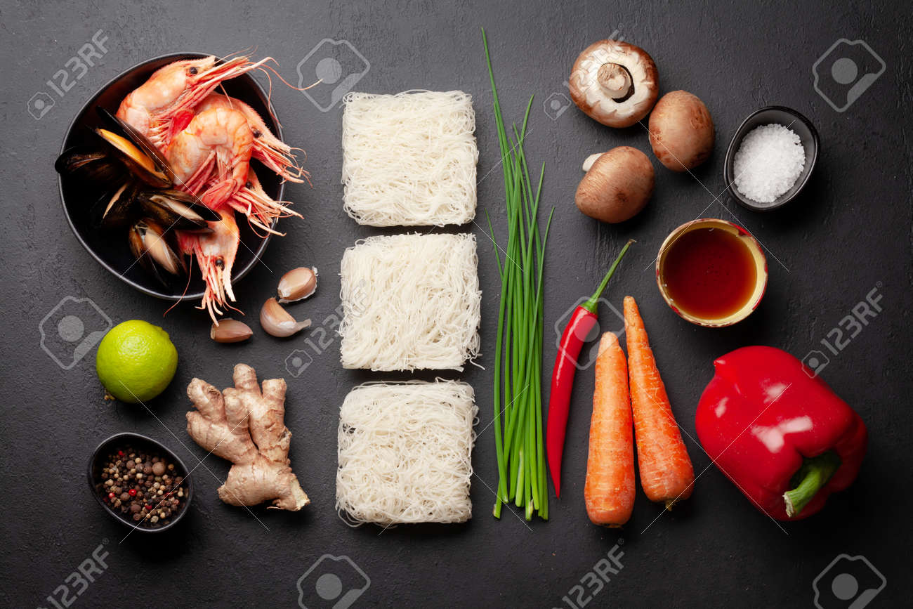 Ingredients for wok cooking with stir fried noodles, shrimps and vegetables on stone background. Top view flat lay - 169549870