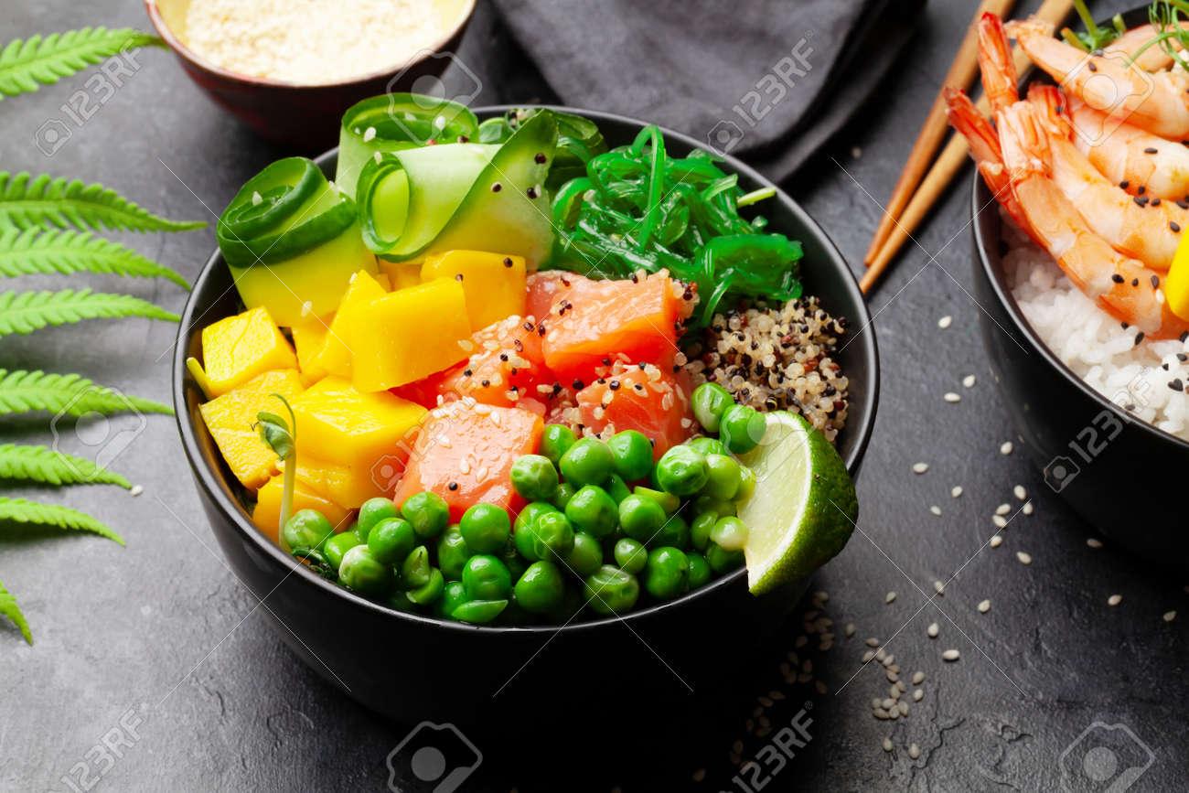 Poke bowls with shrimps, salmon, avocado and mango. Traditional hawaiian meal - 169549880