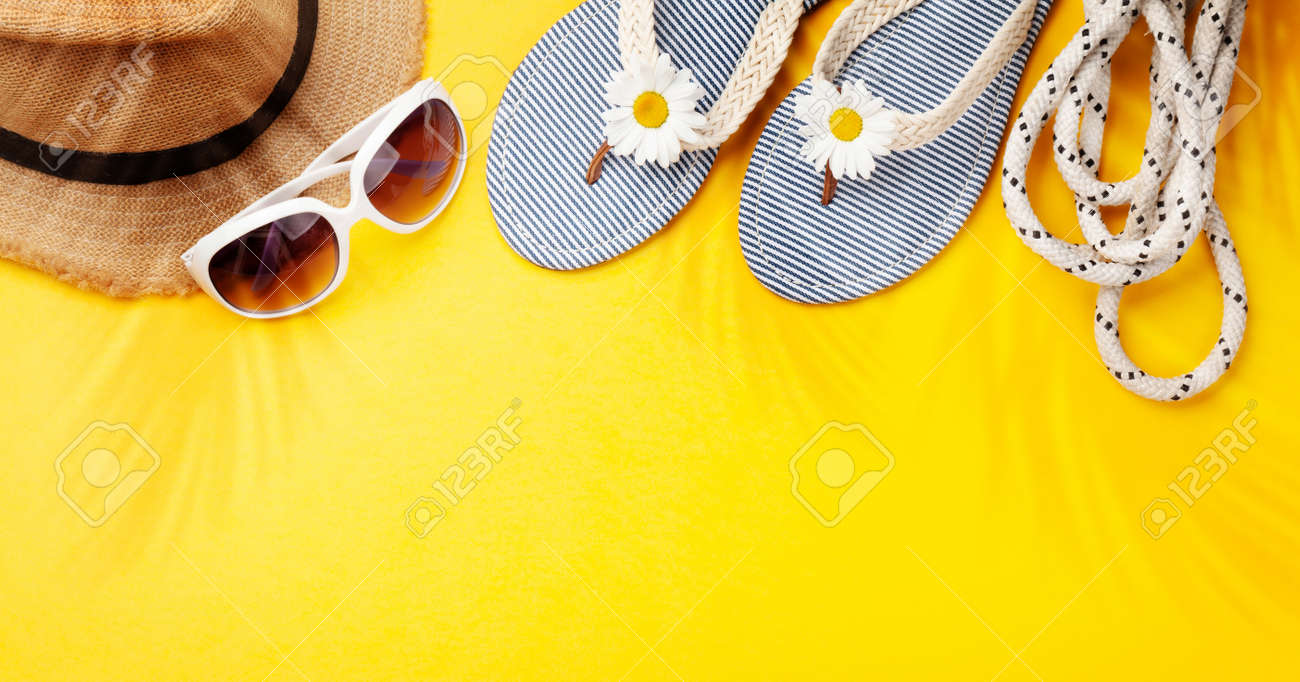 Summer vacation items and accessories. Flip flops, sunglasses and sun hat on yellow background. Top view flat lay with copy space - 169549887