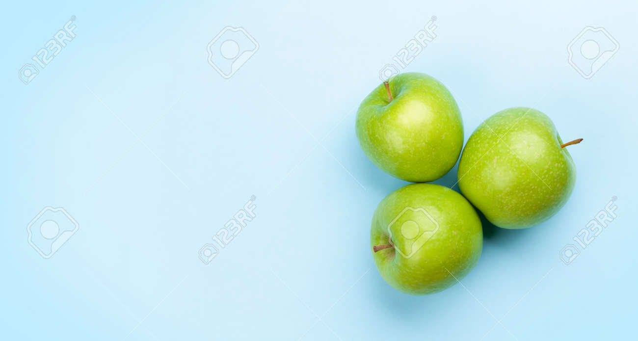 Fresh ripe green apple fruits on blue background. Top view flat lay with copy space - 169549908