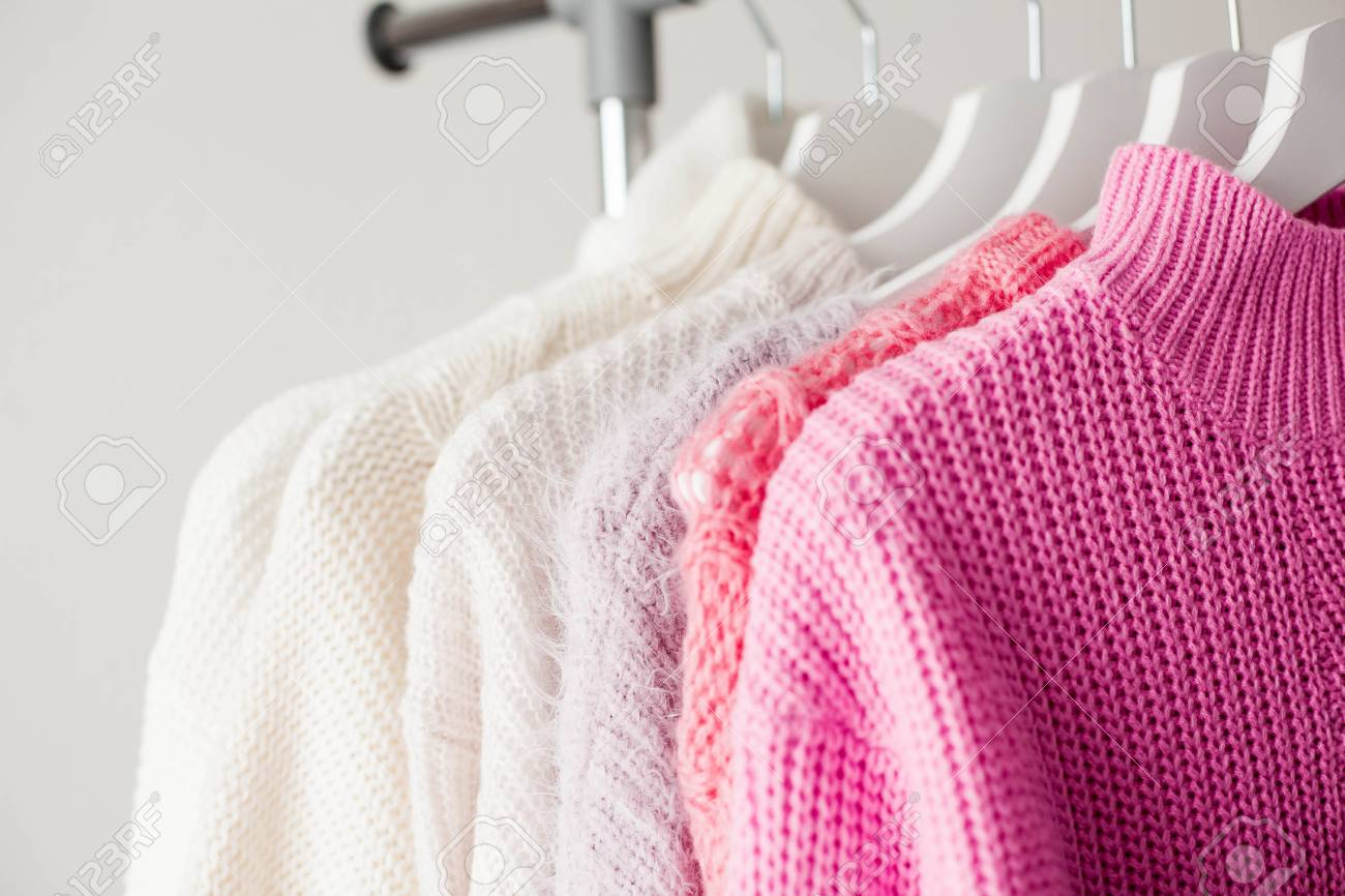 A hanger with things. Knitted sweaters hang on hangers. Bright..