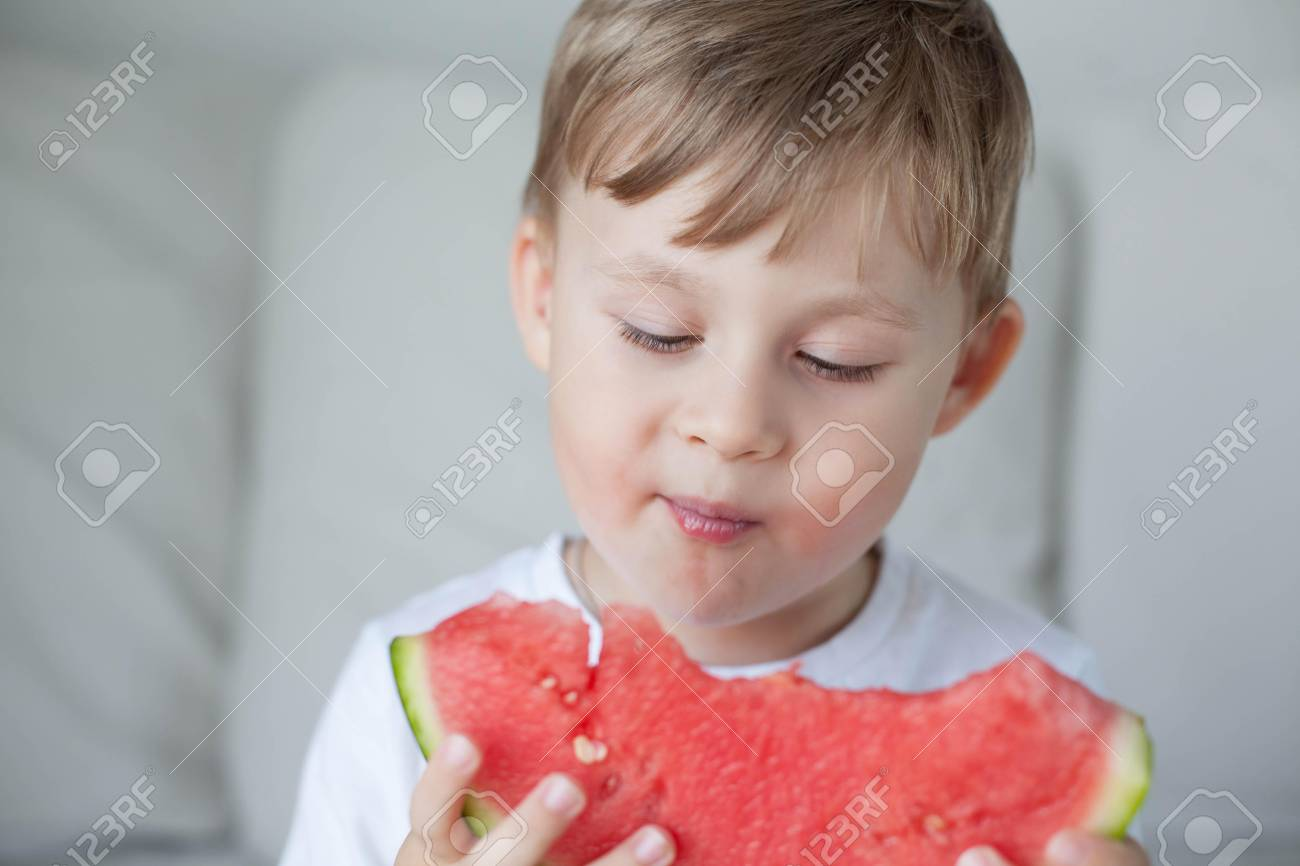 A small cute boy 4 years old is eating a watermelon. Summer. Heat.