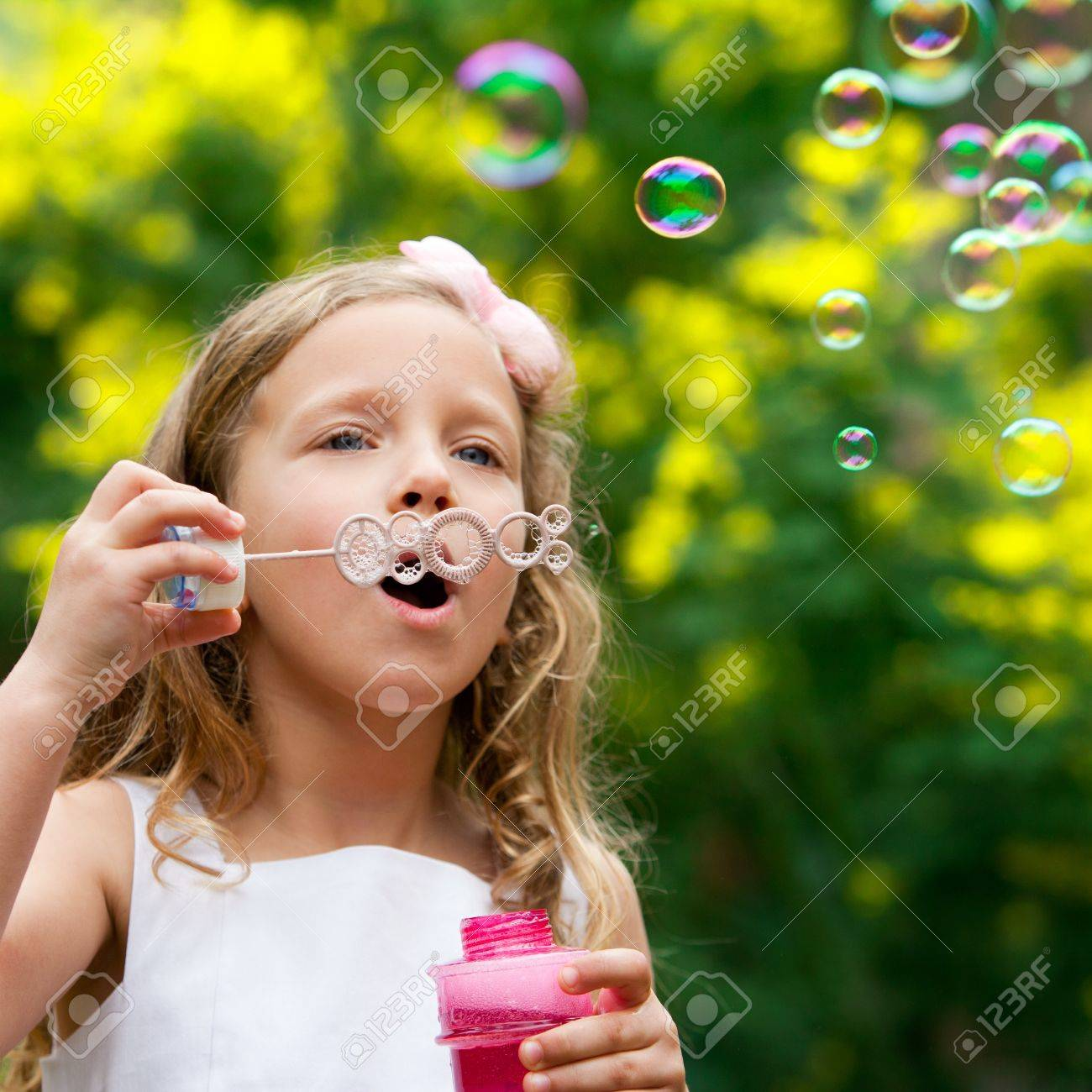 Close up of cute little girl blowing bubbles outdoors Stock Photo - 12671671