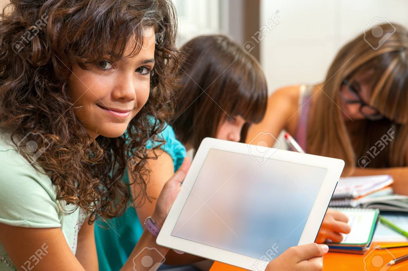 Portrait of young student at desk showing digital tablet with blank copy space Stock Photo - 15432073