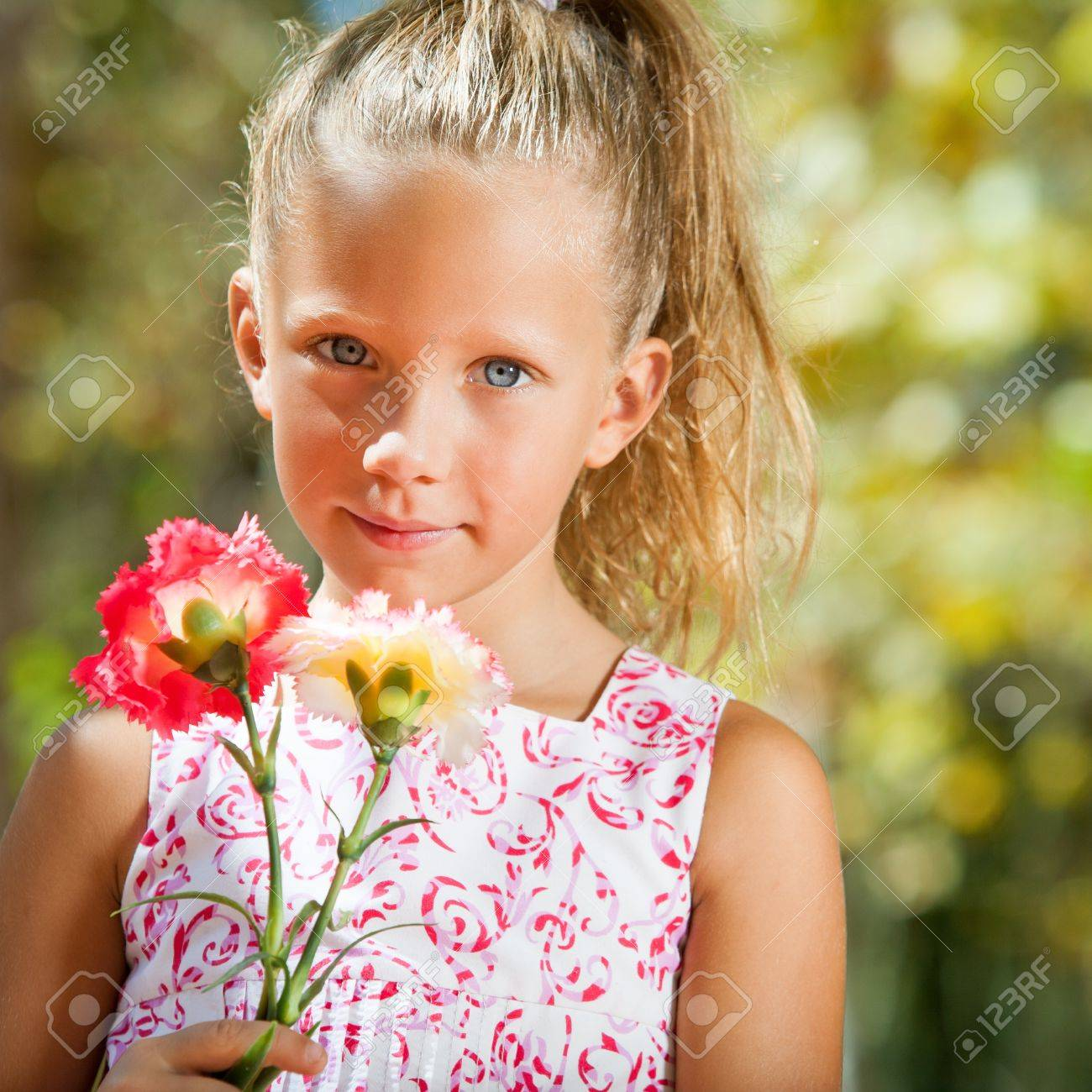 Close up portrait of cute girl holding flowers in garden. Stock Photo - 15404485
