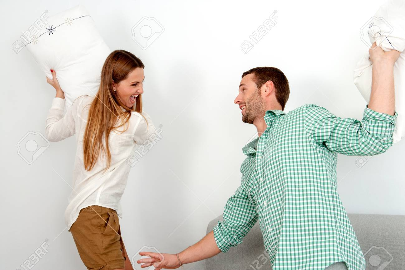 Young attractive couple having pillow fight in room. Stock Photo - 17238279
