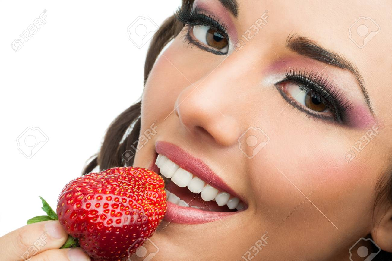 Extreme close up of attractive woman eating strawberry. Stock Photo - 19386470