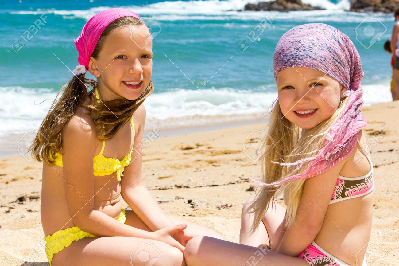 83e6b8c1ed Portrait of two kids in swimwear sitting next to sea Stock Photo - 20357604