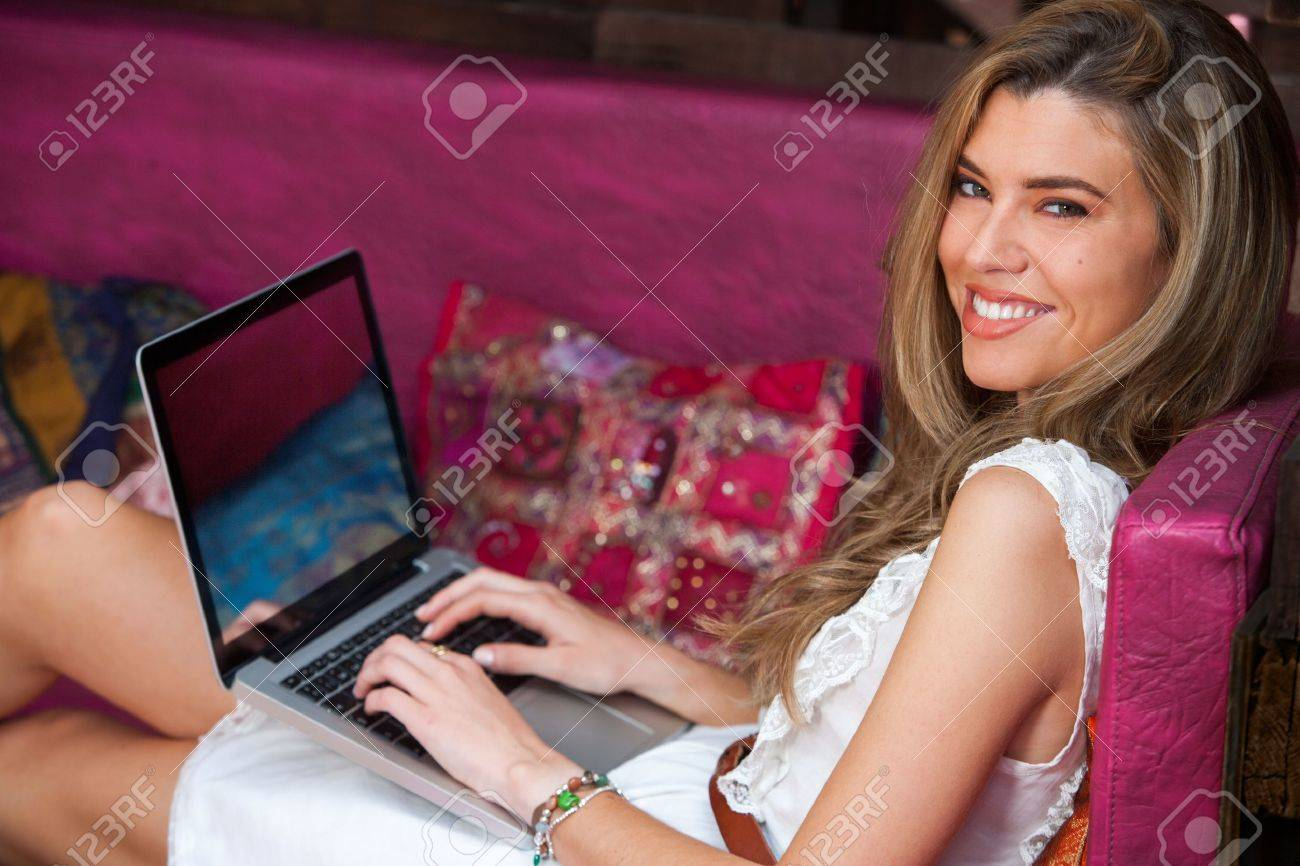 Portrait of cute blond girl relaxing with laptop on couch. - 21576471