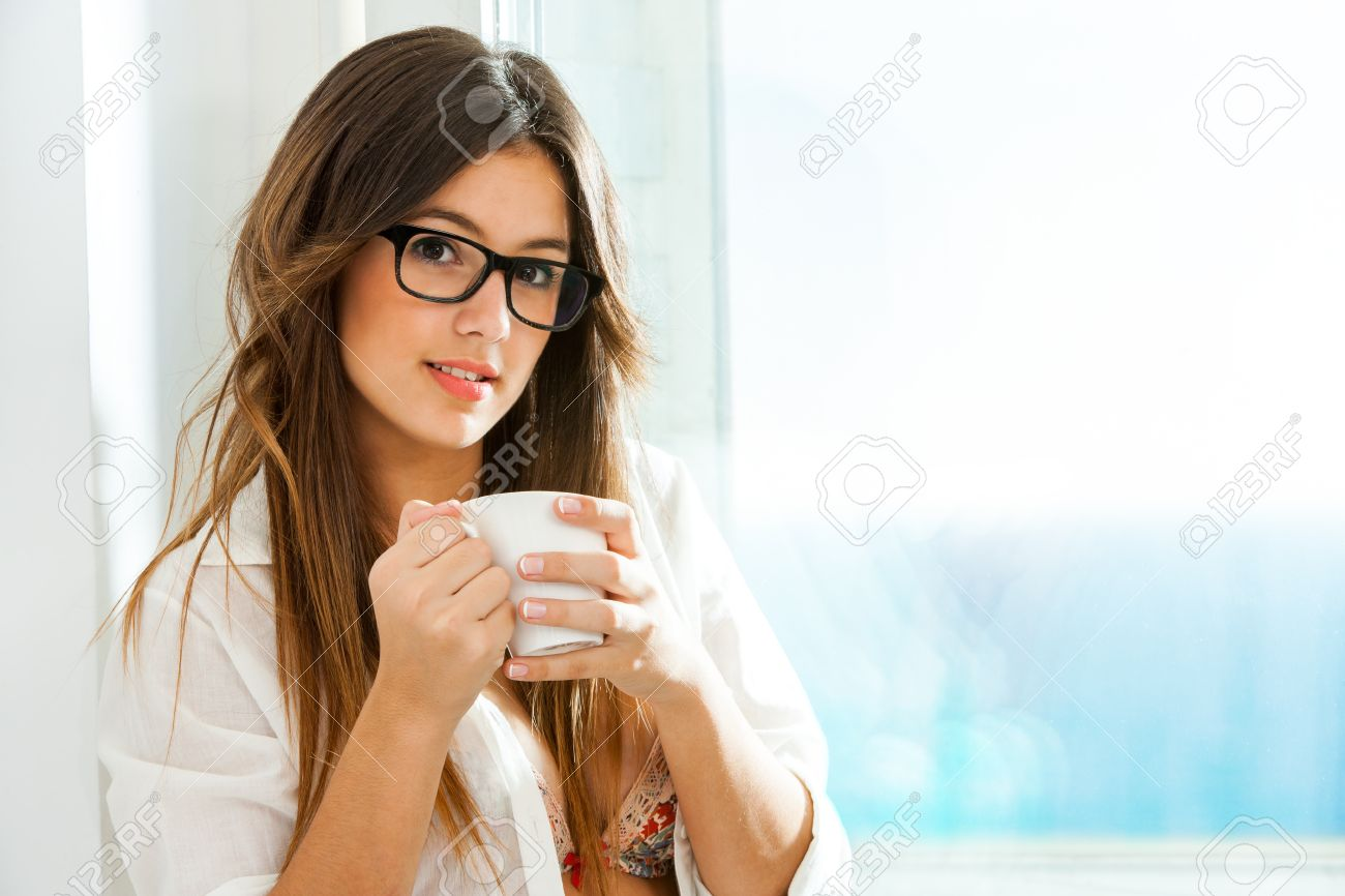 Close up portrait of cute girl with coffee mug next to window with sea view. Stock Photo - 23099775
