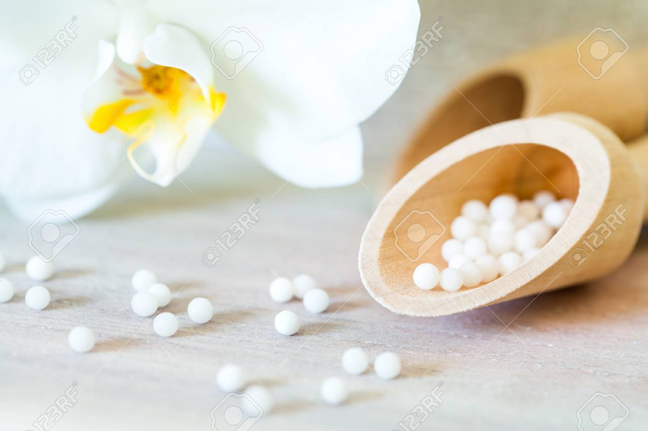 Macro close up of homeopathic balls with orchid. - 45294699