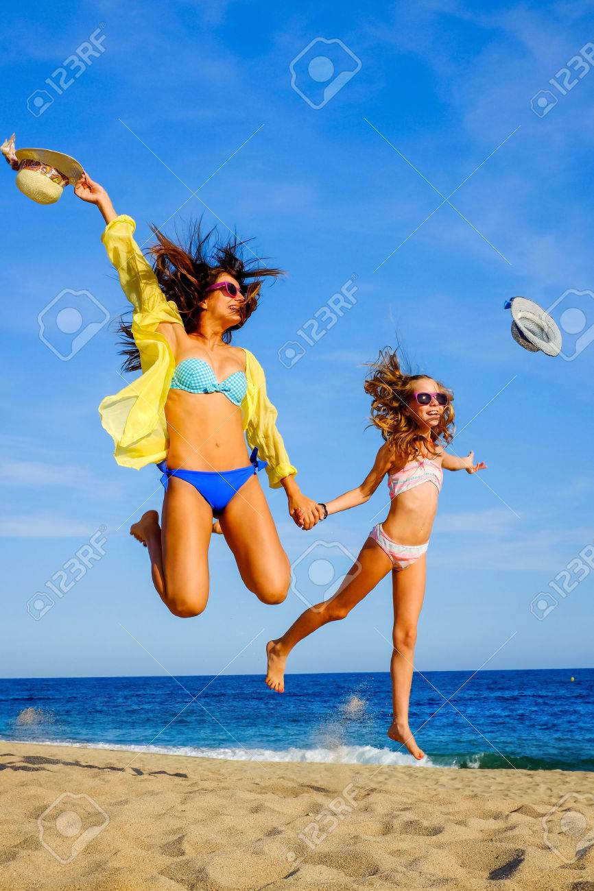 3249f08a42fce Close up action portrait of Young girls in swimwear jumping on beach. Two  attractive happy
