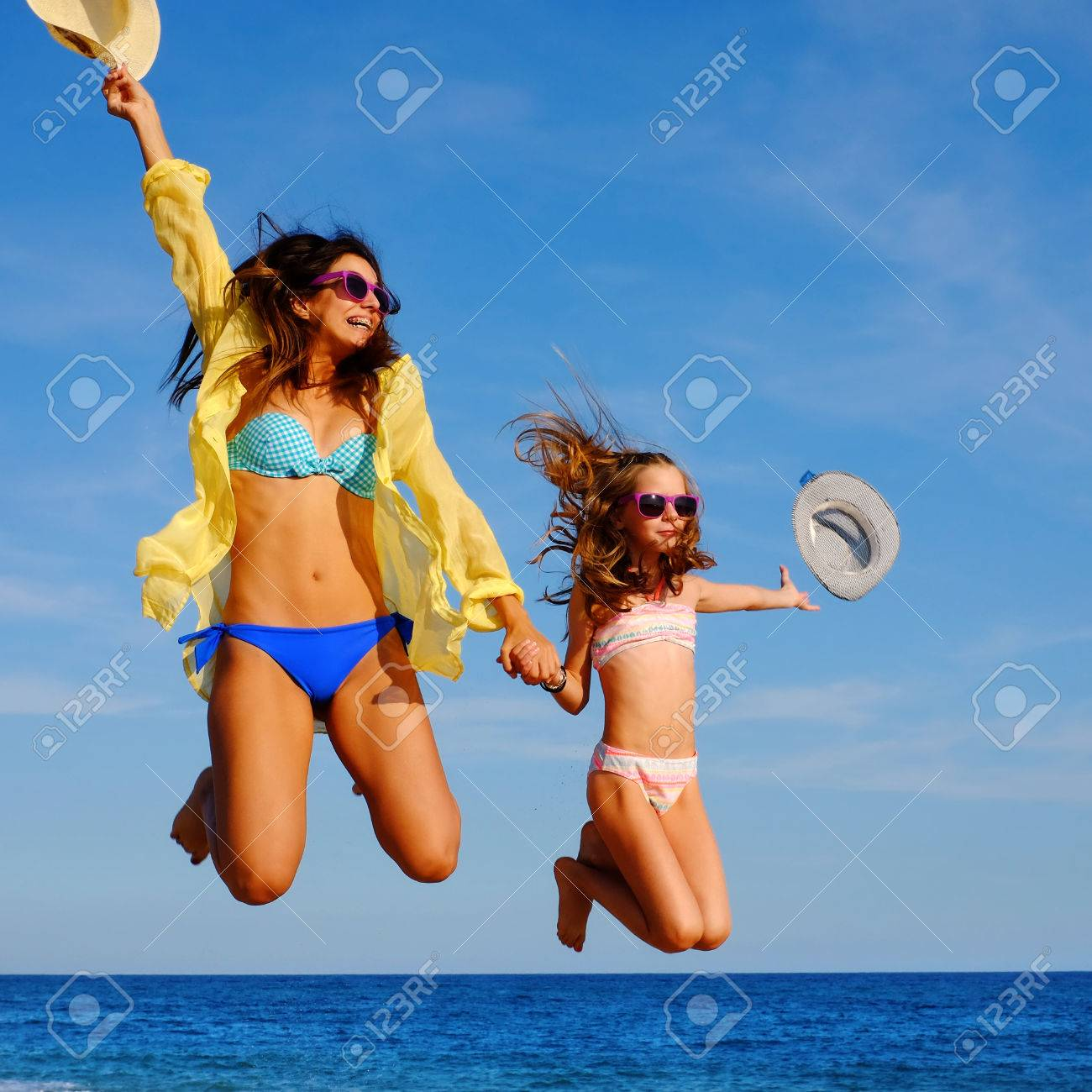 c93ff67e0fe6c Close up action portrait of young girls on holiday jumping on beach. Two  attractive happy