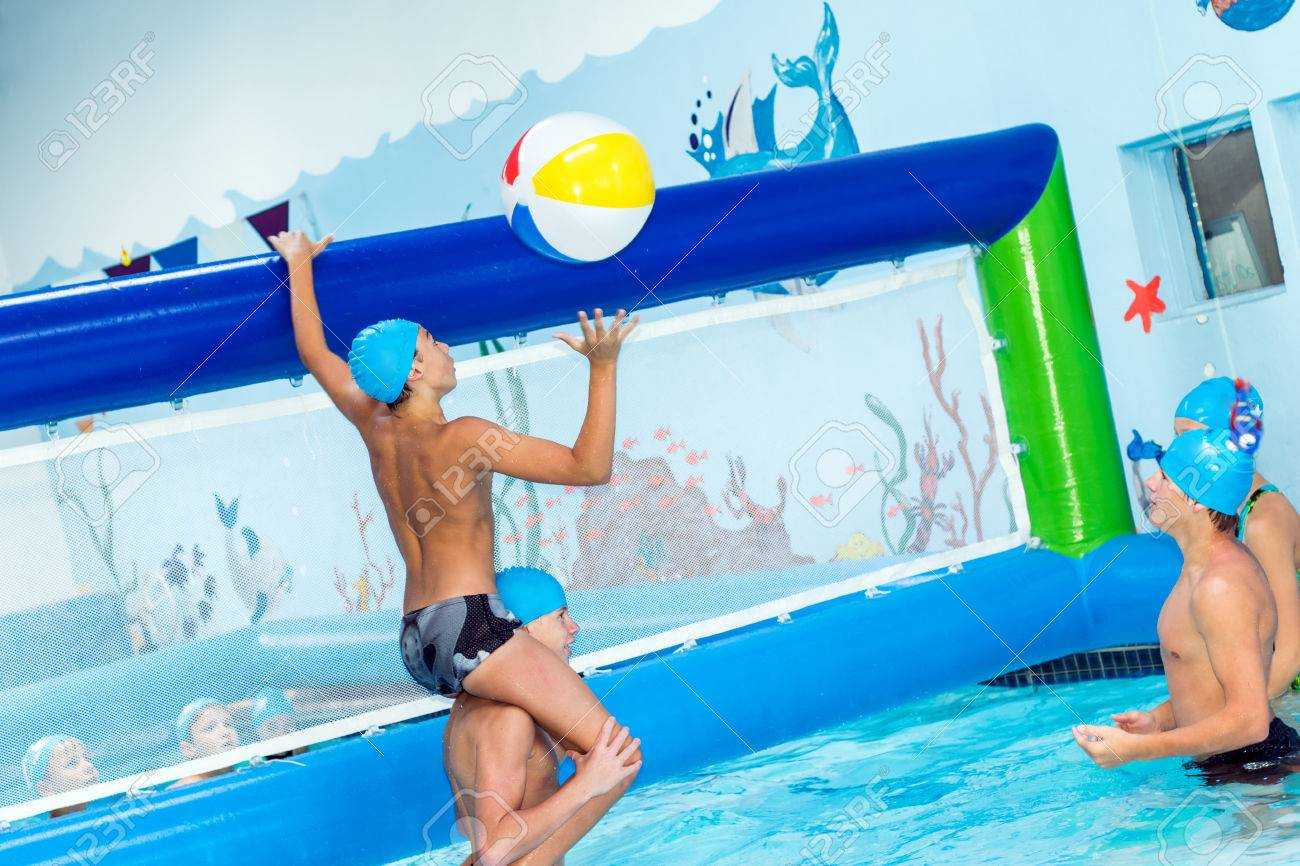 Action shot of children playing water volleyball in indoor swimming..