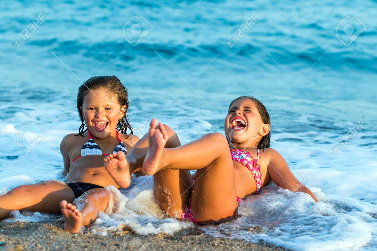 33a48c7815 Close up portrait of two little girls having fun together in waves. Stock  Photo -