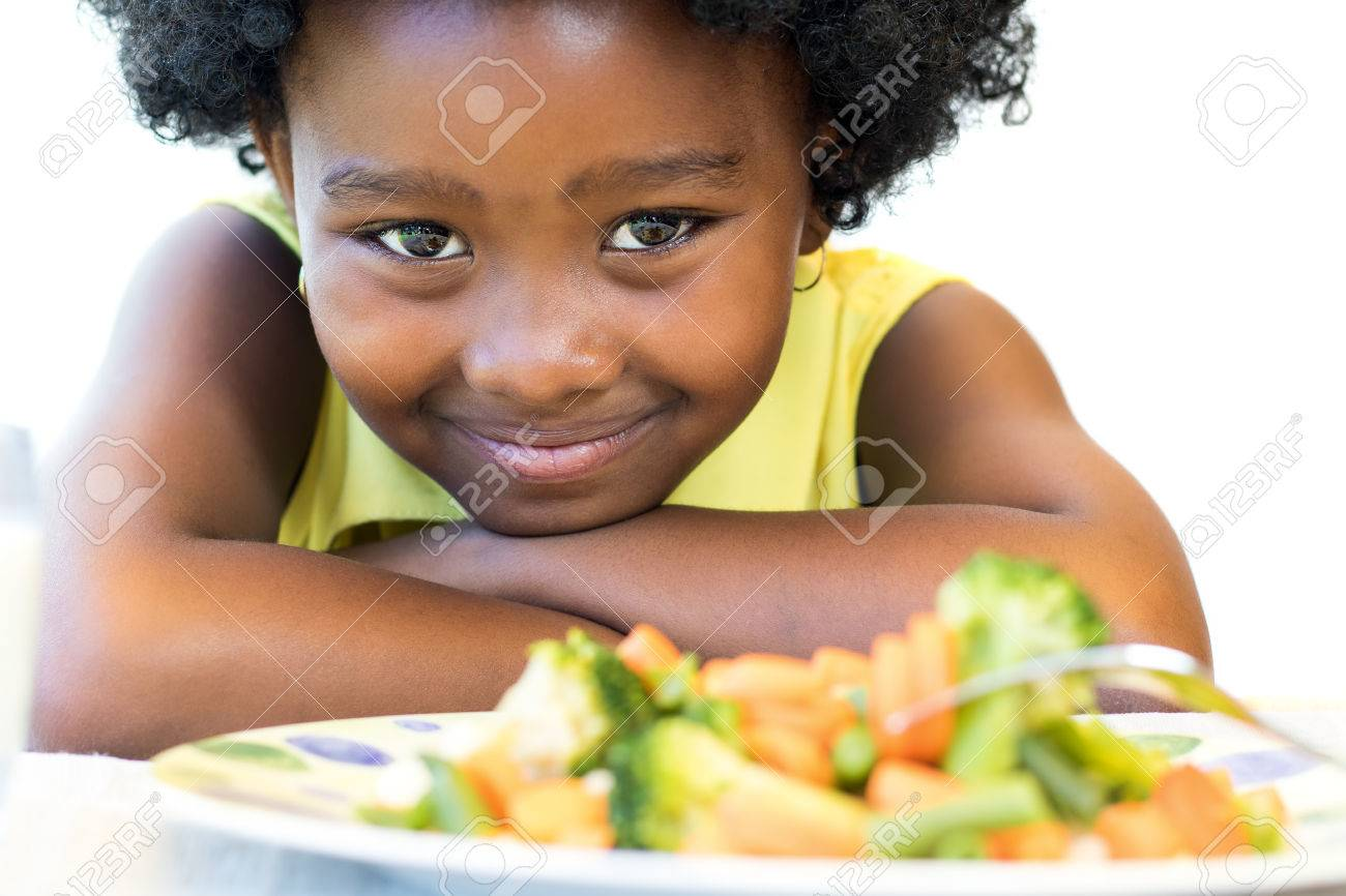 Close up face shot of cute African girl in front of healthy vegetable dish. Isolated on white. - 66647649