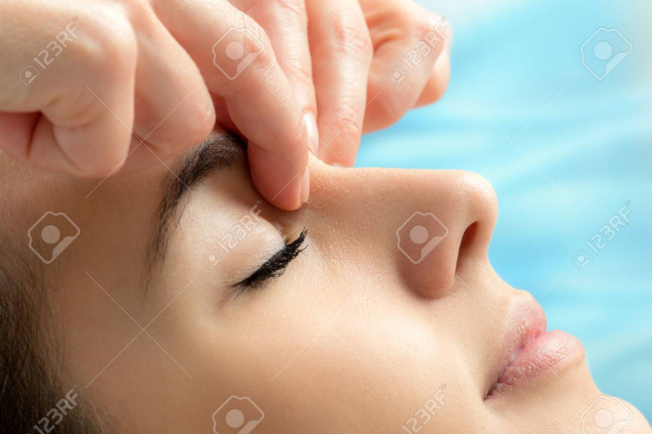 Extreme Close Up Of Hands Applying Pressure Between Eyes On Young