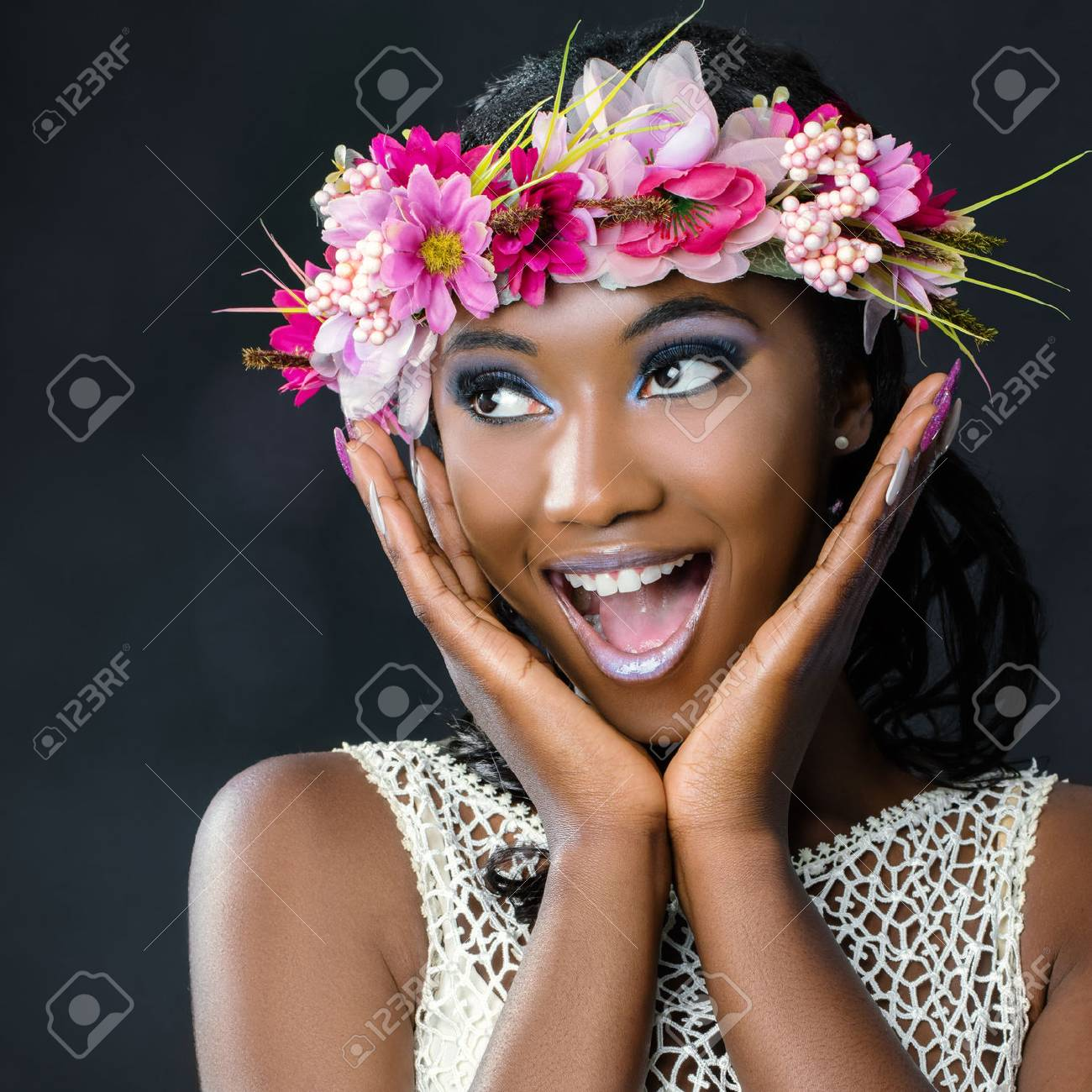 Close up fun portrait of attractive young african bride wearing colorful flower garland.Girl pulling funny face with hands next to face looking at corner. - 89934085