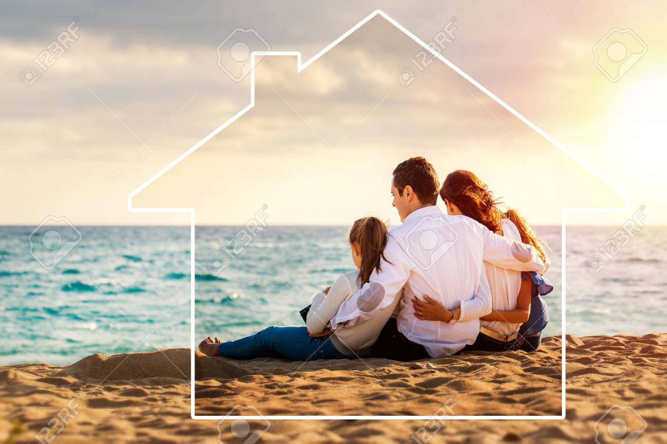 Conceptual late afternoon outdoor portrait of young parents sitting on beach with kids.Foursome giving back against sea and cloud background. House icon drawing around family. - 119595700
