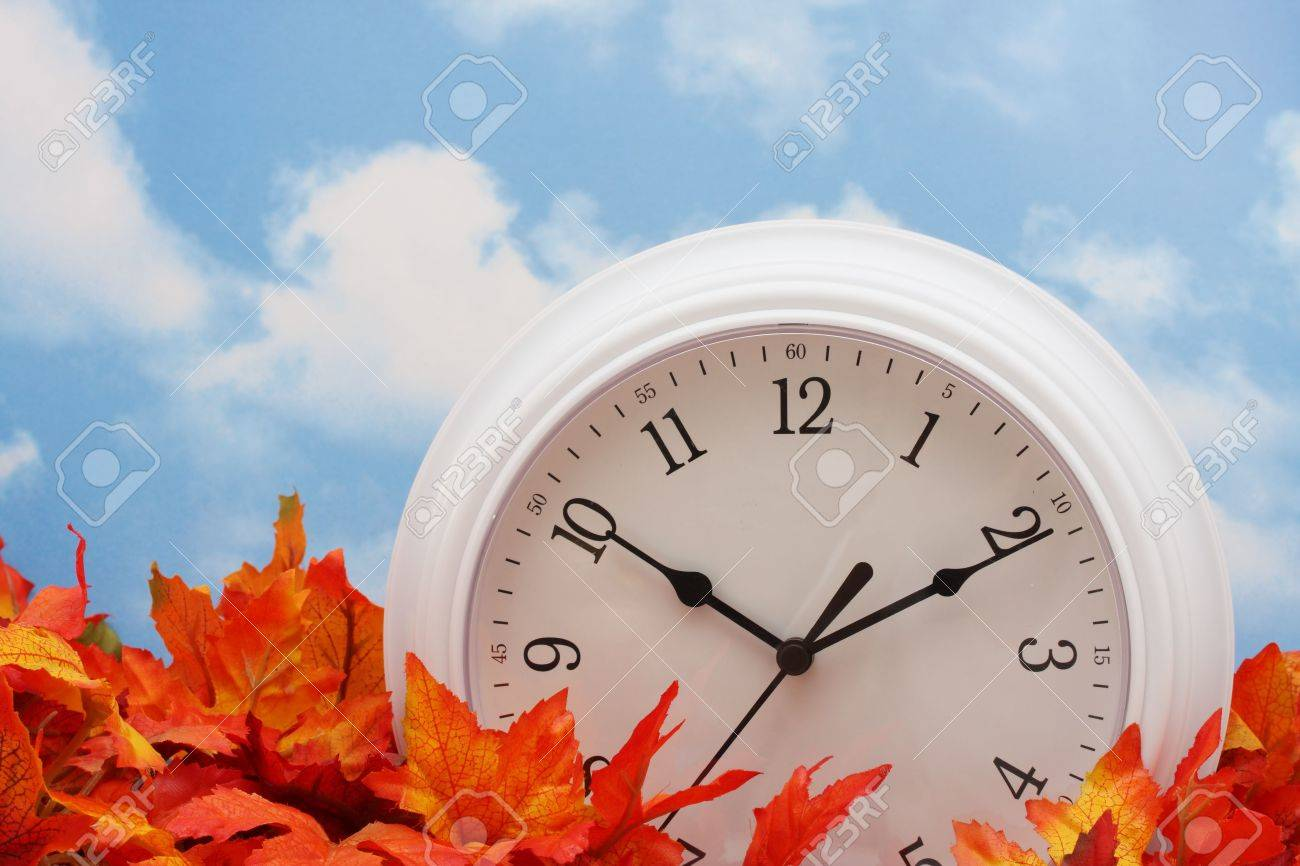 white clock on fall leaves, sky background Stock Photo - 1849642