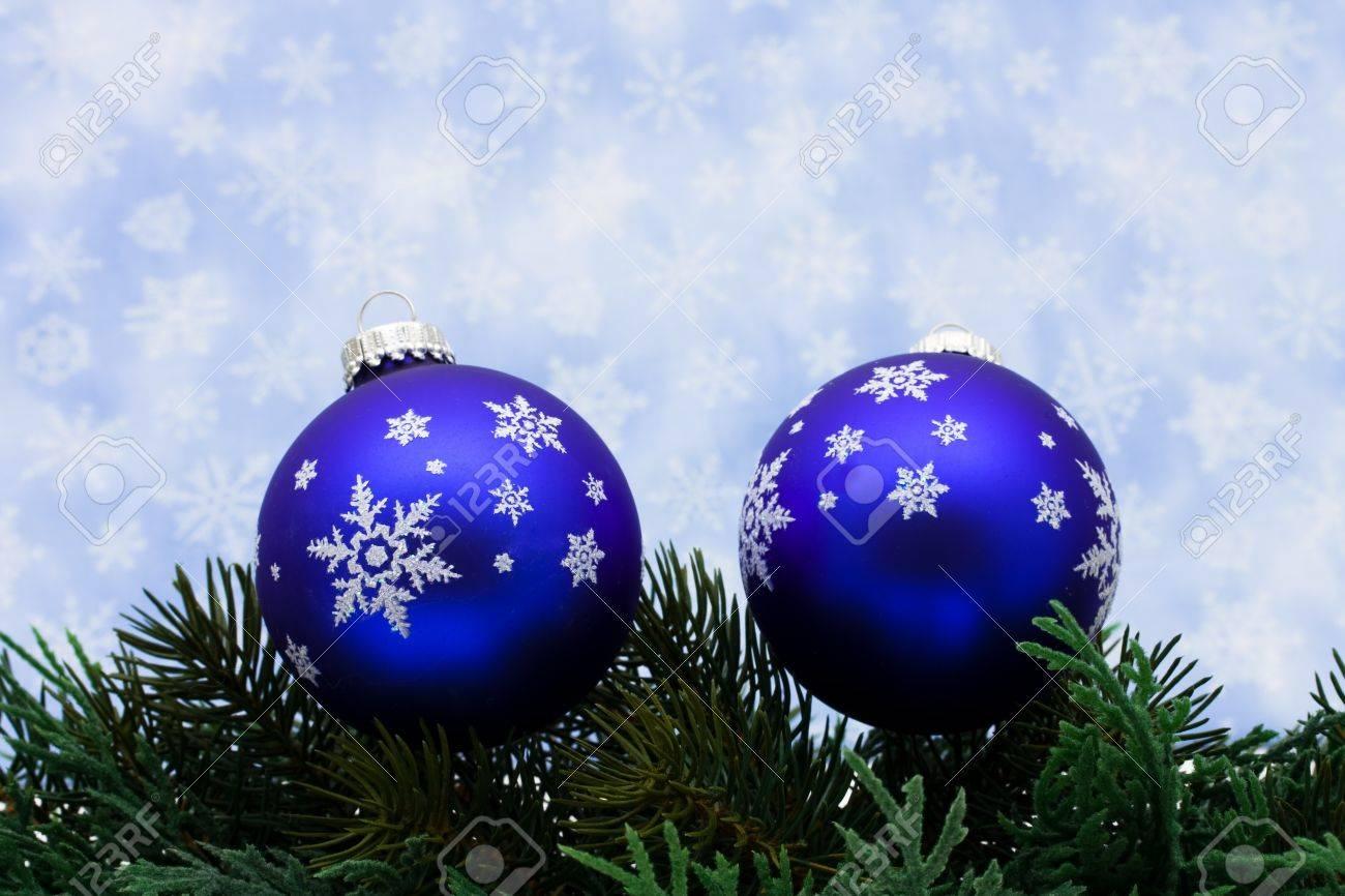 Christmas Tree Limb With Blue Glass Ball Ornaments On Snowflake Background Border Stock Photo
