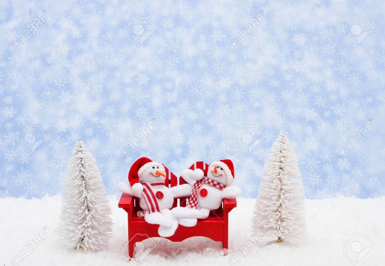 White evergreen trees sitting with a snowman on snow with a blue snowflake background, snowman Stock Photo - 5750572