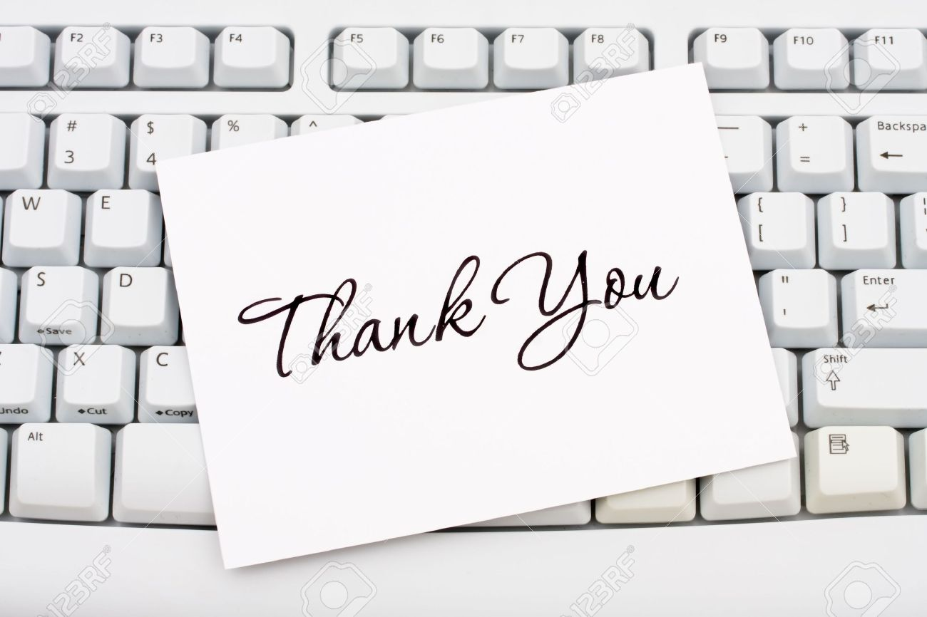 a thank you card sitting on a computer keyboard online thank