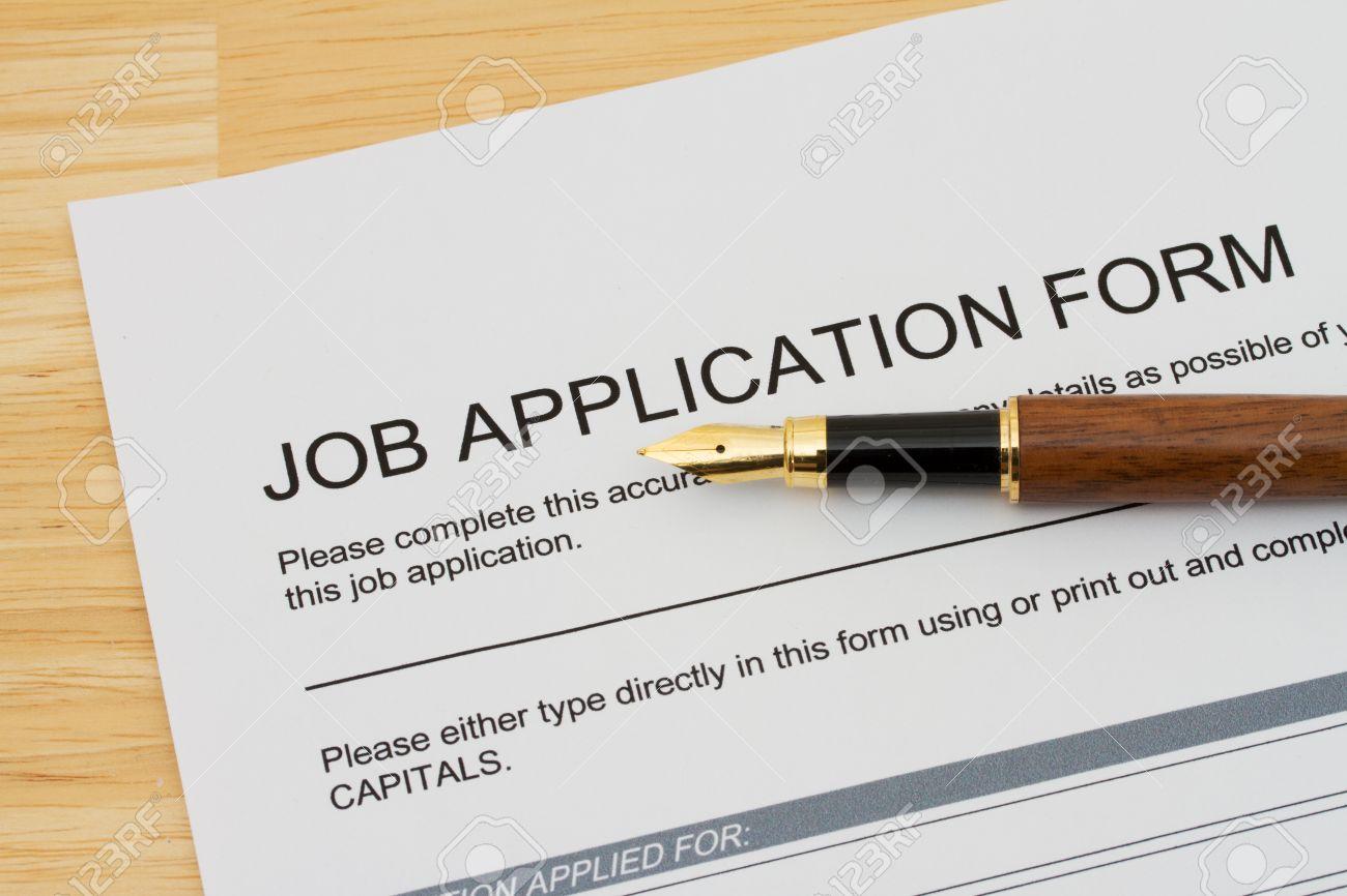 a wooden fountain pen on a wooden desk a job application a wooden fountain pen on a wooden desk a job application form applying for