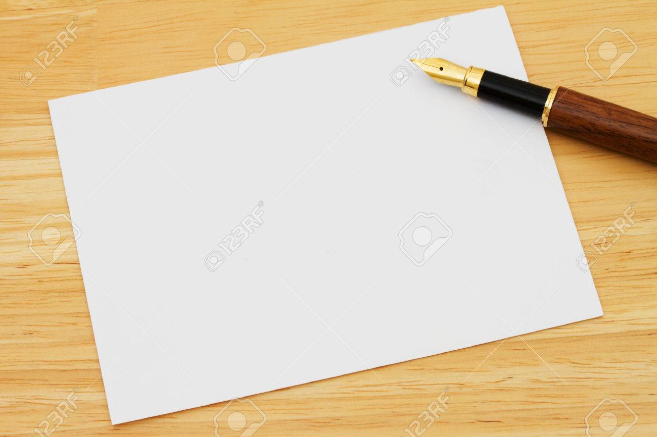 a blank card with a fountain pen on a wooden desk writing a stock