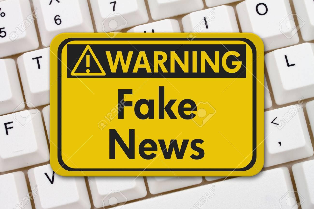 Fake news warning sign, A yellow warning sign with text Fake News on a keyboard - 69384057