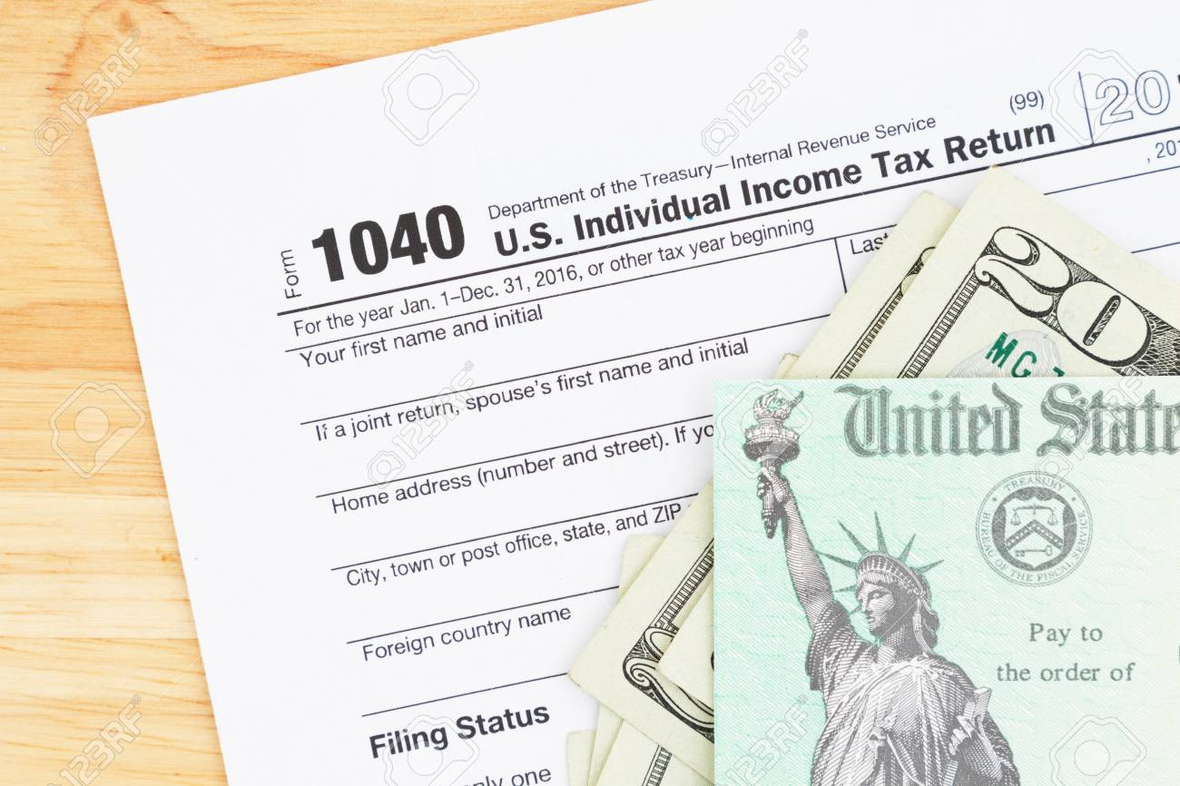 A us federal tax 1040 income tax form with money and refund a us federal tax 1040 income tax form with money and refund check on a wood falaconquin