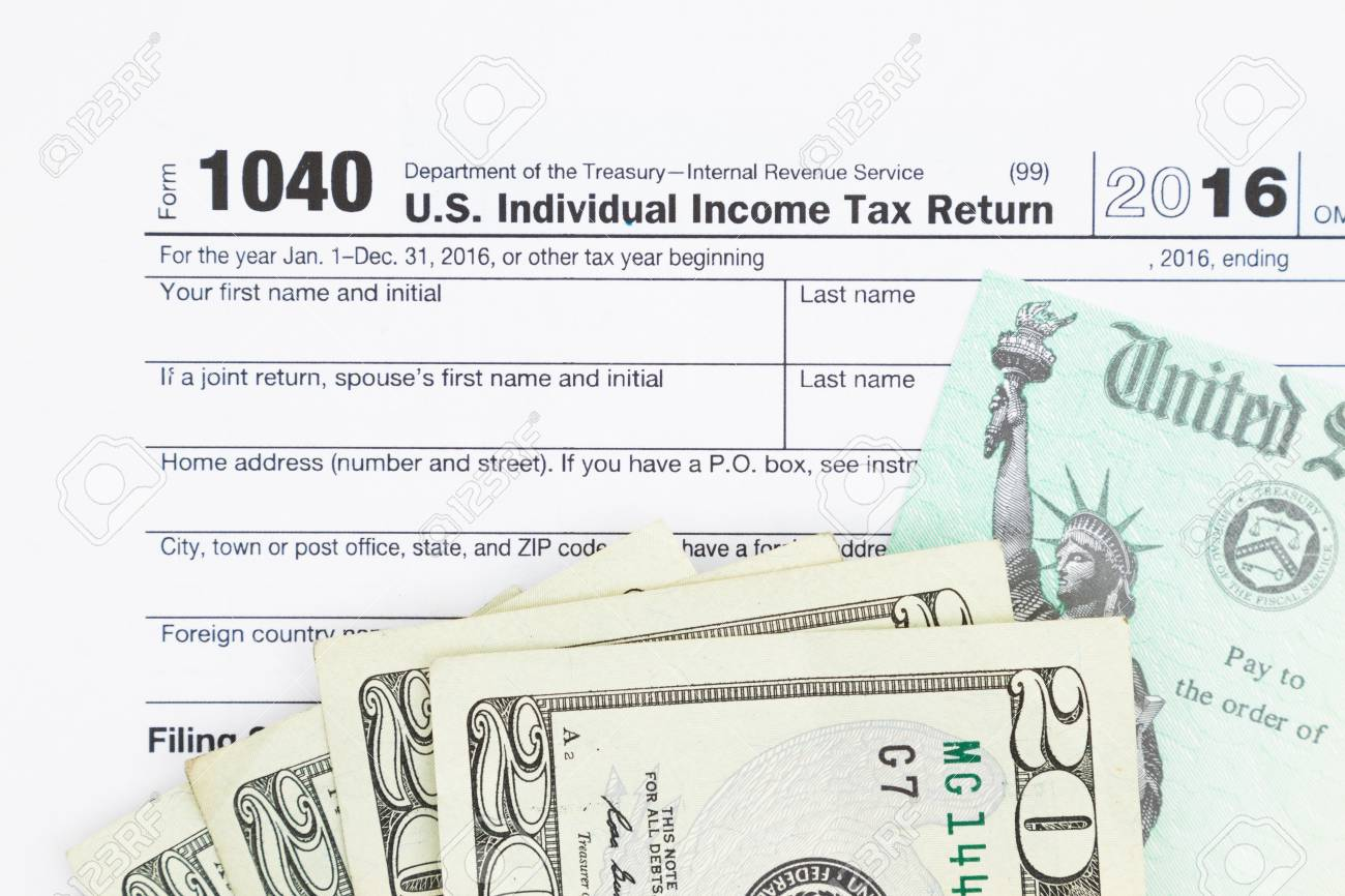 a us federal tax 1040 income tax form with money and refund check stock photo - Federal Tax Form